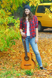 Full length portrait of young guitar player woman at yellow minibus and autumn yellow fallen leaves background Stock Photos