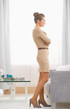 Full length portrait of young housewife standing in living room Royalty Free Stock Photography
