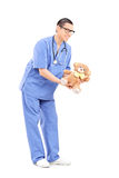 Full length portrait of a young male doctor giving a teddy bear Royalty Free Stock Photo