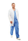 Full length portrait of a young male doctor in a medical surgical blue uniform in motion leaving the operating room royalty free stock photography