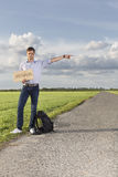 Full length portrait of young man with anywhere sign gesturing on countryside Royalty Free Stock Image