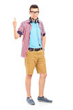 Full length portrait of a young man with headphones giving a thu Stock Photos