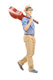 Full length portrait of young man holding an acoustic guitar ove. R his shoulder isolated on white background Stock Images