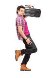 Full length portrait of a young man holding a radio and leaning Stock Photography