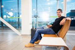 Young Man With Mobile Phone And Laptop At Airport. Full length portrait of young man with mobile phone and laptop in airport waiting area Royalty Free Stock Photos