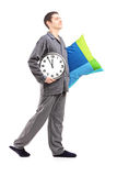 Full length portrait of a young man with pillow and clock Royalty Free Stock Image