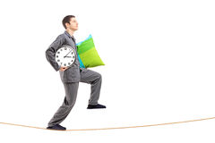 Full length portrait of a young man with a pillow and clock slee Stock Image