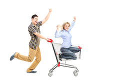 Full length portrait of a young man pushing a woman in a shopping cart. Full length portrait of a young men pushing a women in a shopping cart on white royalty free stock photo