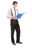 Full length portrait of young man reading papers Stock Photos