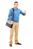 Full length portrait of a young man with a shoulder bag giving a. Thumb up isolated on white background Royalty Free Stock Photo