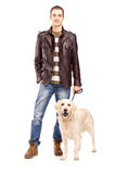 Full length portrait of a young man standing with a dog Stock Photography