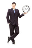 Full length portrait of a young man in suit holding a clock Stock Photo