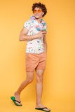 Full length portrait of a young man in summer clothes. Full length portrait of a smiling young man in summer clothes holding cocktail while walking isolated over stock photography