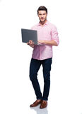 Full length portrait of a young man using laptop Stock Photos