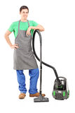 Full length portrait of a young man with a vacuum cleaner Stock Image