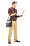 Full length portrait of a young man working on laptop stock photo