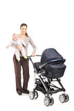 Full length portrait of a young mother with a baby and a pushcha Stock Photo