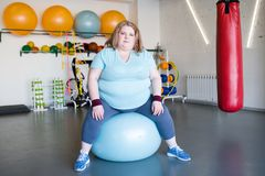 Obese Woman in Fitness Club. Full length portrait of young obese woman sitting on fitness ball looking at camera, copy space Stock Image