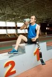 Handicapped Running Champion. Full length portrait of young paralympic champion sitting on winners pedestal and drinking water taking break from running practice stock photography