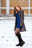 Full length portrait of young pretty redhead woman in blue dress and grey coat at winter outdoors Royalty Free Stock Images