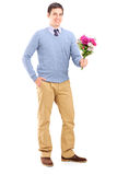 Full length portrait of a young romantic man holding a bouquet  Stock Photos