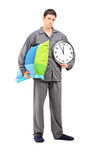 Full length portrait of young sleepy guy holding a wall clock an stock photography