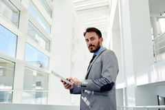 Full length portrait a young smart managing director holding touch pad while standing in big white hallway Royalty Free Stock Photography