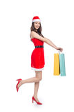 Full length portrait of a young smiling asian woman holding shopping bags before christmas Stock Image