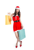Full length portrait of a young smiling asian woman holding shopping bags before christmas. Stock Photos