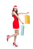 Full length portrait of a young smiling asian woman holding shopping bags before christmas Royalty Free Stock Images