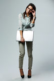 Full-length portrait of a young smiling businesswoman holding laptop Royalty Free Stock Image