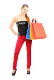 Full length portrait of a young smiling female holding bags Royalty Free Stock Photo