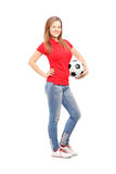 Full length portrait of a young smiling female holding a soccer Royalty Free Stock Images