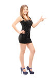 Full length portrait of a young smiling woman in a dress pointin Royalty Free Stock Photography