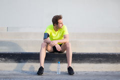 Full length portrait of young sports man thoughtful looking away while taking break after workout training outdoors Royalty Free Stock Images