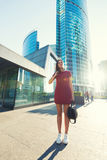 Full length portrait of a young stylish hipster girl with trendy look standing near modern office building in sunny summer evening Stock Photo