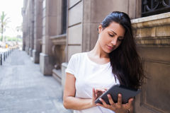 Full length portrait of a young stylish hipster girl working on her digital tablet computer while standing on the street in urban Stock Images