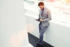 Full length portrait of a young successful man entrepreneur dressed in elegant clothes using touch pad Stock Image