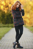 Full length portrait of young trendy redhead woman  in scarf and plaid jacket with autumn foliage background outdoors Stock Photography