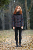 Full length portrait of young trendy redhead woman in scarf and plaid jacket with blurred forest background outdoors Royalty Free Stock Photo
