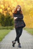 Full length portrait young trendy redhead woman in scarf and plaid jacket on park path with autumn foliage background cold season Stock Images