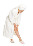 Portrait of woman in bathrobe checking leg Stock Photography