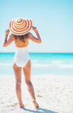 Full length portrait of young woman on beach. rear view Royalty Free Stock Image