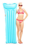 Full length portrait of a young woman in bikini holding a swimmi Royalty Free Stock Images