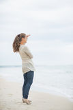Full length portrait of young woman on cold beach Royalty Free Stock Image