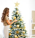 Young woman decorating christmas tree wi Royalty Free Stock Photos