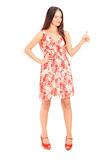 Full length portrait of a young woman in a dress giving a thumb Royalty Free Stock Photos