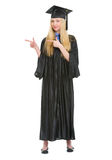 Woman in graduation gown pointing on copy space Royalty Free Stock Image