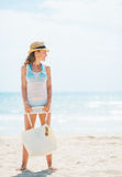 Full length portrait of young woman in hat and with bag on beach Royalty Free Stock Photo