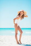 Full length portrait of young woman in hat on beach Stock Images
